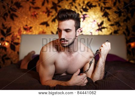 Sexy macho man holding handcuffs on bed in hotel room bdsm poster