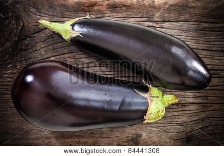 Fresh Eggplants With Leaves Over Dark Background