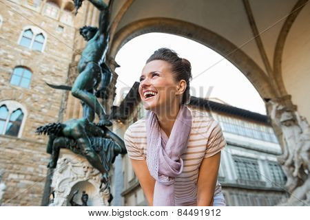Smiling Young Woman In Front Of Statue Perseus With The Head Of