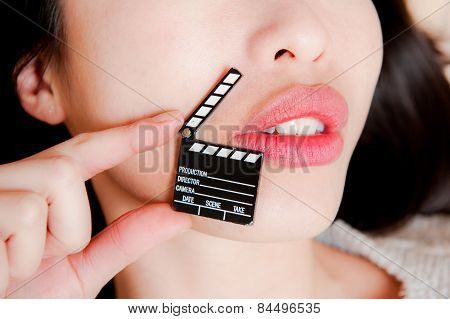 Face detail of sensual woman lips no eyes with hand holding little movie clapper board poster