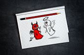 Angel And Devil Doodle Drawing on Notepad page as concept of conscience and moral dilemma in fight of good and evil. poster