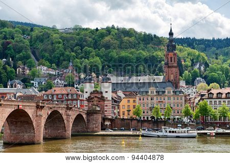 Old Bridge Over Neckar River with View of Old Town Heidelberg, Baden-Wurttemberg, Germany Nestled in Lush Green Foothills on River Bank