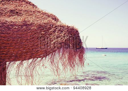 closeup of a rustic umbrella made of natural fibers on a nice beach in Ibiza, Spain, with a clear blue seawater in the background, with a retro effect