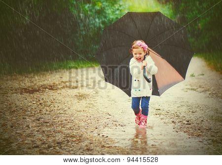 Happy Baby Girl With An Umbrella In The Rain Runs Through