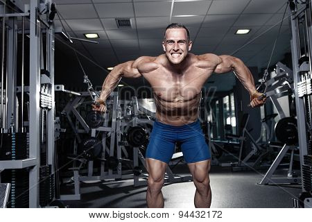 Muscular Bodybuilder Guy Doing Exercises Workout In Gym