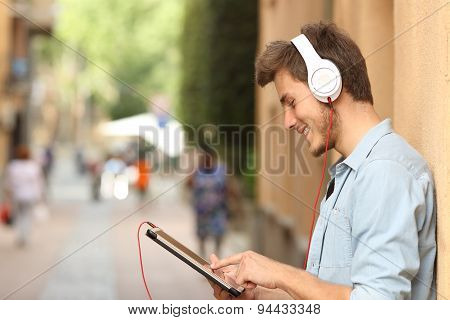 Man Using A Tablet With Headphones On The Street