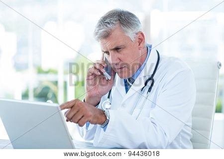 Serious doctor working on laptop and having phone call in medical office