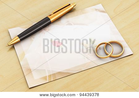Wedding rings, pen and empty card on wooden table