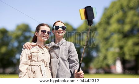 people, children, friends and technology concept - happy girls taking picture with smartphone on selfie stick over park background