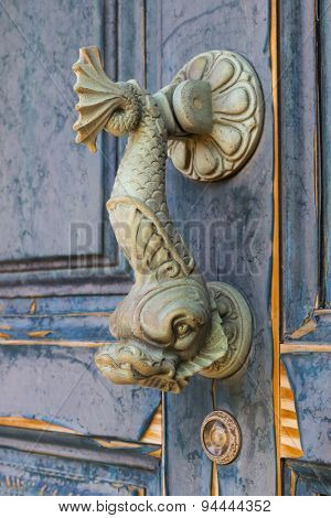 Doorknocker in the form of a fish on an old door