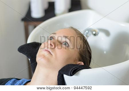 Young woman in a hairdressing salon lying back with her head in the basin waiting for her hair to be shampooed before cutting it poster