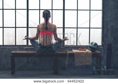 Rear View Of Woman On Bench In Lotus Position In Loft Gym