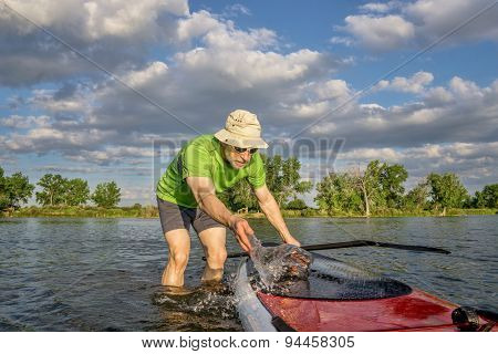 male paddler is washing his SUP paddleboard before starting workout on a local lake in Colorado