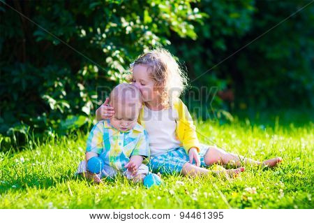 Happy Children Playing In The Garden With Toy Balls