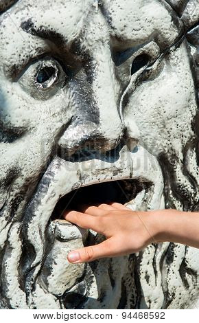 Stone Face With Hand In Mouth