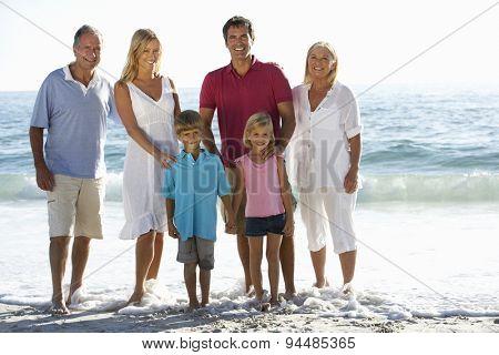 Three Generation Family On Holiday Walking On Beach