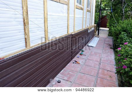 Installation of brown plastic siding on the facade of the house poster