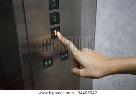 A woman pressing the Elevator to down to the 1 floor