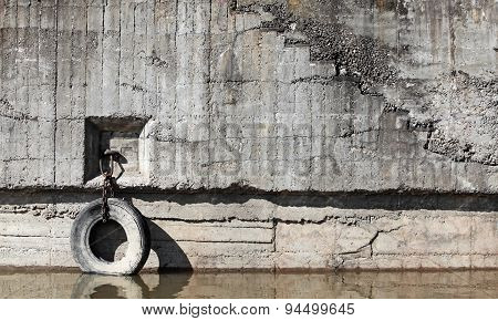 Old concrete mooring wall with automotive tire hanging on chain as a bumper poster