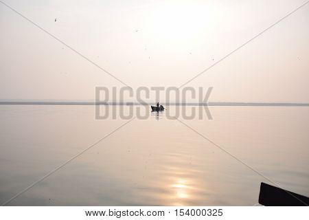 Boat with fishermen floating on river Ganga during sunrise, Varanasi, Uttar Pradesh, India