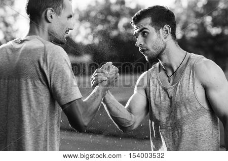 Black and white portrait of two young handsome men with arm wrestling