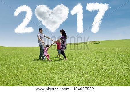 Joyful Asian family playing on the meadow while celebrate new year day with cloud shaped numbers 2017 on the sky