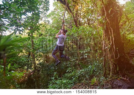 hanging on liana young women hiking in forest