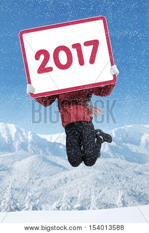 Image of woman jumping and holding number 2017 on the board while celebrating new year in the winter season