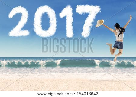 Back view of young woman holding hat while jumping in the beach with cloud shaped number 2017