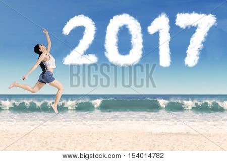 Image of attractive young woman jumping in the beach with cloud shaped number 2017 on the sky