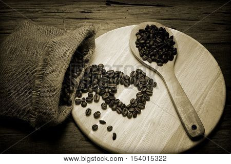 heart from coffee beans on old wood