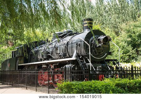 Old fashioned steam train in the public park as a memorial. Black train with red wheels.