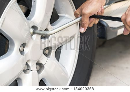 Removing the wheel nut with a wrench.