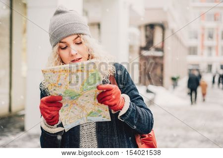 Young blond curly female tourist in warm clothes and red gloves with London map looking for a way in winter city blurred white background with people