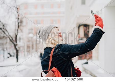 Young blond curly female tourist in warm clothes and red gloves with London map making selfie winter city blurred background