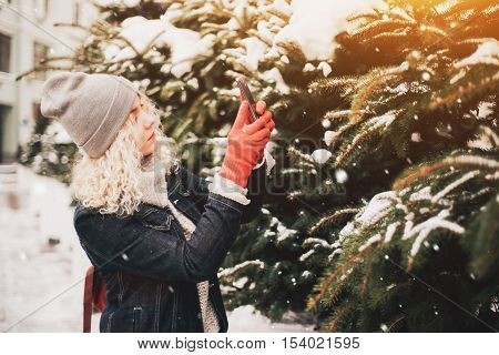 Young blond curly female tourist in warm clothes and red gloves making photo of spruce on a smartphone