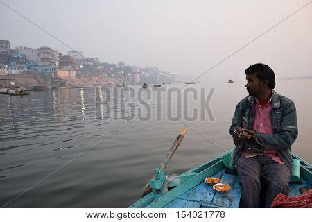 VARANASI, UTTAR PRADESH, INDIA - FEBRUARY 17, 2016 - Unidentified indian boatman on his boat on river Ganga at sunrise