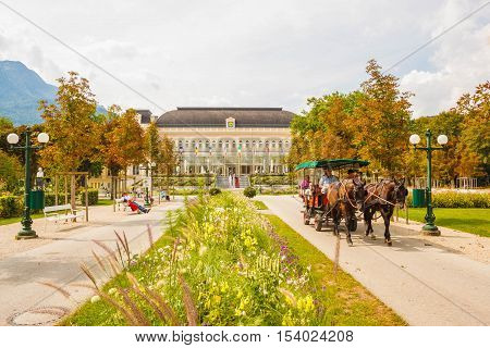 Bad Ischl Austria - September 2 2016: A horse-drawn carriage with tourists rides through a park in front of the Congress and Theaterhouse (Kongress & Theaterhaus) in Bad Ischl Austria.