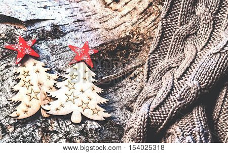 Christmas ornaments are located on a tree bark and warm knitted sweater