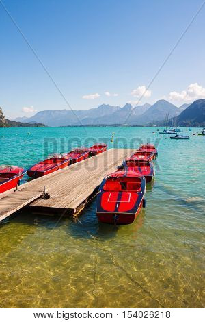 Red boats on transparent water of alpine lake Wolfgangsee near St.Gilgen Austria