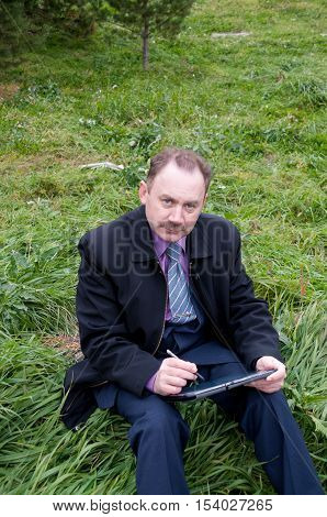 Man is sitting with a tablet in nature