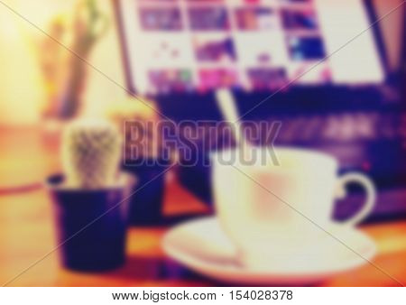 Blurred coffee cup and laptop on wooden table. vintage tone style