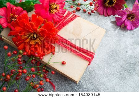 Old book with red zinnias and autumn berries