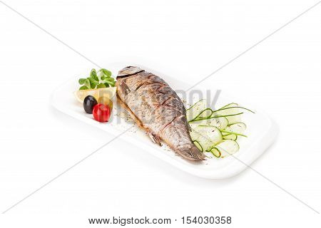 Isolated delicious - the freshly cooked, fried fish - crucian served with a cucumber, an olive and a lemon on a white dish.