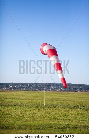 Windsock in a background of the green field and a grass at a light breeze.