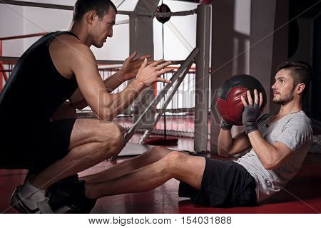 Throwing back. Young handsome bearded man training abdomen while throwing ball to with his trainer.