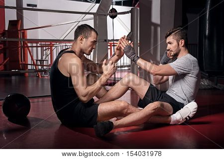 Fierce fighting. Two handsome concentrated men practicing martial arts while sitting on the floor in sports club.