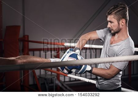 During training. Side view of young bearded trainer wearing boxing gloves while practicing kick boxing hook on ring.
