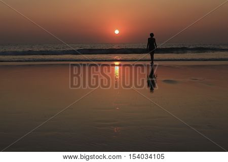 female silhouette on the beach at sunset time