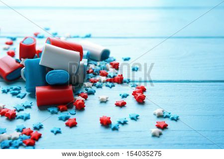 Delicious candies and scattered sprinkles on blue wooden background